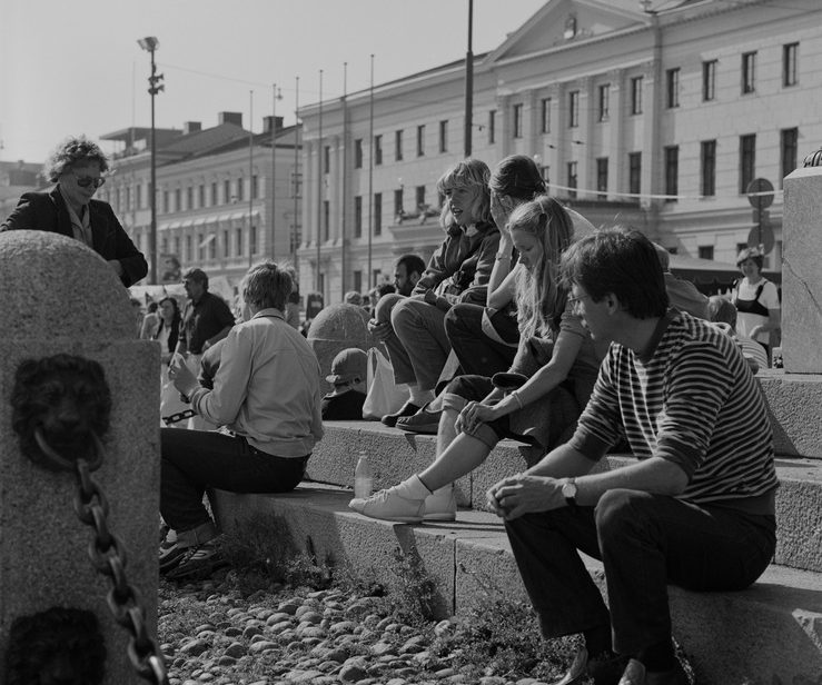 Kauppatori. Ihmisiä istumassa Keisarinnan kiven jalustalla.